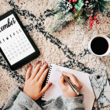 Calendar flat lay. A young millenial writing on a notepad with a calendar on a tablet beside her. A cup of coffee, mobile phone and a piece of christmas decoration on a rug.