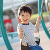 Cute little Asian boy enjoying swing at the modern playground