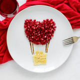 Art food concept. Air balloon with couple. Lace pancakes with pomegranate seeds. Top view. Flat lay. Space for copy