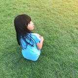 High angle view of a little Asian girl in blue t shirt sitting on green field smiling and looking away from camera.