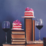 Two pices of cake and glasses of red wine on books
