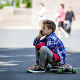 RIGA, LATVIA - MAY 22, 2015: The boy sits on a skateboard and talk on the telephone.