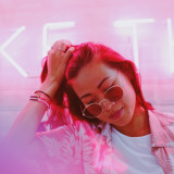 Young hipster girl with pink neon light