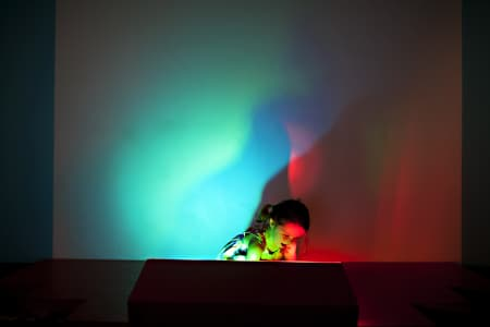 girl playing in red, blue, and yellow light