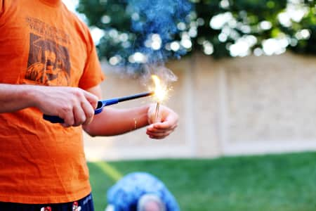 man lighting sparkler for fourth of july