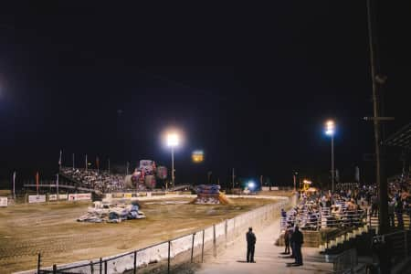 A monster truck jumps a row of cars at the county fair.