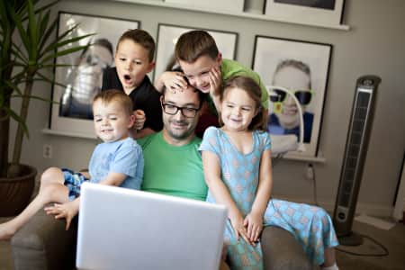 four kids sitting on dad's lap and facetime chatting with grandparents over the internet