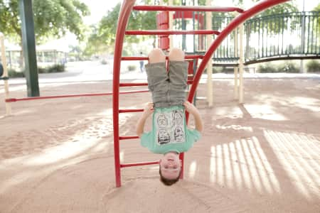 boy hanging upside down on playground equipment at the park
