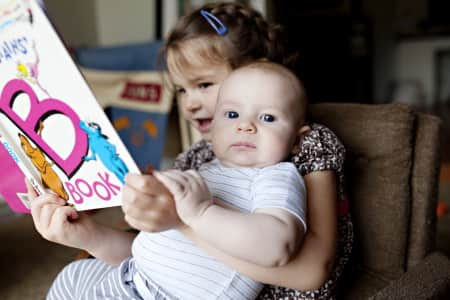 Little girl reading book to baby brother