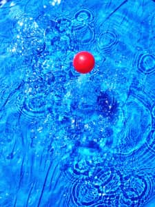 Red ball splashing in blue pool of water