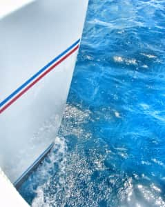 The hull of a catamaran cutting through the impossibly blue waters of the Caribbean.