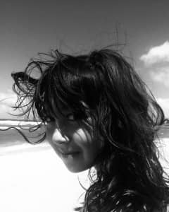 Girl with wind blown hair on the beach. Smiling mischievously.