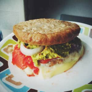 Two turkey burger parties with tomato, red onion, cheese, and guacamole