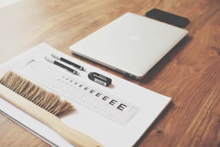 A designers toolkit: MacBook Pro, iPhone 6plus, grid paper, two pencils, ruler, eraser, and brush.