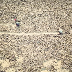 """Petanque is a form of boules where the goal is to throw hollow metal balls as close as possible to a small wooden ball called a cochonnet (literally 'piglet') or jack, while standing inside a circle with both feet on the ground."""