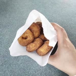 Hand holding a bag of mini donuts