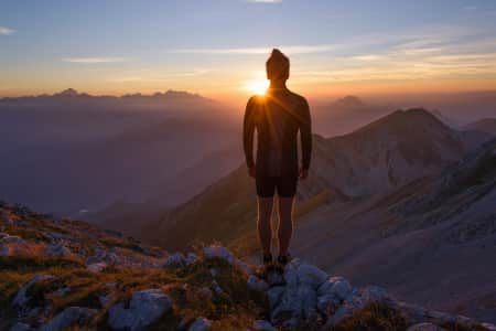 Male hiker observing the sunset at the top of the local big mountain. The photograph was taken in Karavanke mountain range in Slovenia.