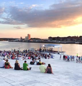 People attending a show near a harbour before sunset
