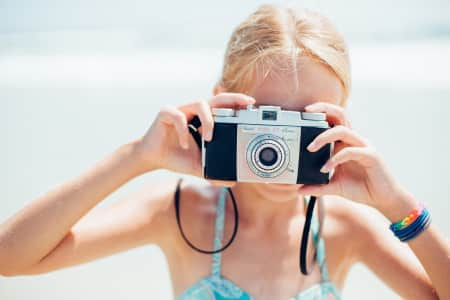 Young girl on beach with vintage film camera.
