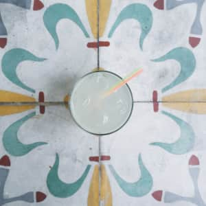 Margarita with neon straws on decorative tile.