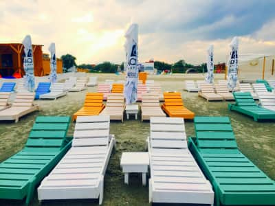 Empty beach with colourful wooden sunbeds