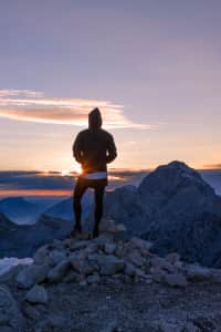 Male hiker in the vast mountain landscape at sunset.