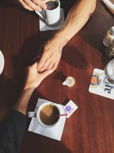 couple having coffee, holding hands