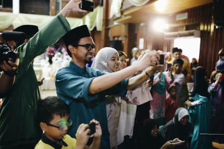 People are busy to photograph and show off their gadgets in a wedding ceremony.