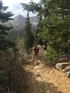 Hiker taking a photo of the beautiful fall scenery in Colorado