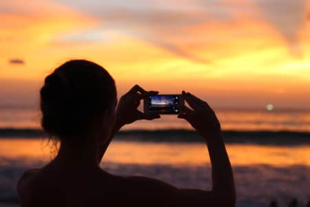 A girl is making photo of sunset on the beach