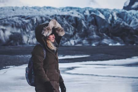Female explorer by a glacier in Iceland