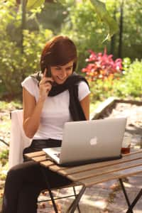 Woman using laptop and phone