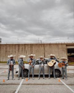 Traditional Mariachis standing and playing their instruments in front of a silver car.