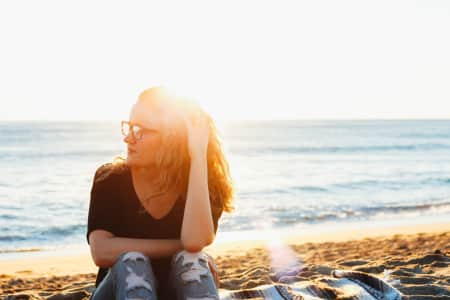 Girl in glasses sitting on the beach watching the sunset.