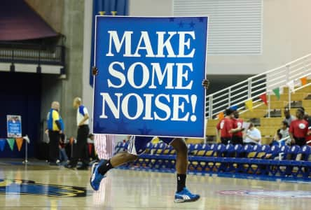 "A member of the Philadelphia 76ers flight squad seen runing off the court hold a sign the reads ""MAKE SOME NOISE!"""