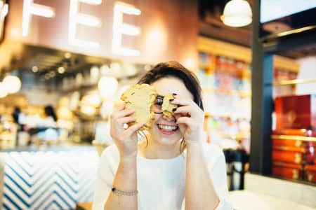 Cute millennial girl at a coffee shop looking through a broken cookie and smiling