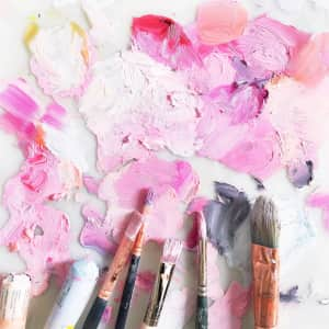Dirty paintbrushes and oil paint sticks on an artist's palette filled with textured pink paint.
