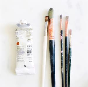 Well used tube of white paint and five artist paintbrushes lined up on a white background.