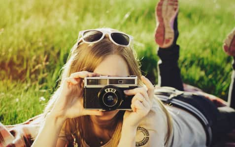 Girl lying in grass taking a picture on a retro camera.