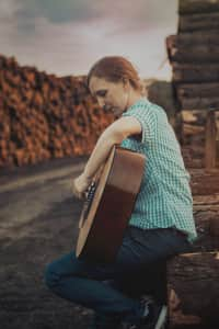 Girl playing the guitar outdoors.