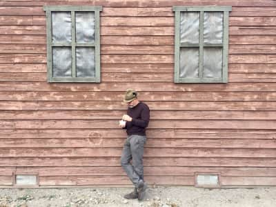 Man eating a bowl of ice cream, standing alone against a wall