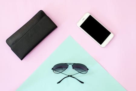 Sunglasses, wallet and smartphone on pink and blue background.