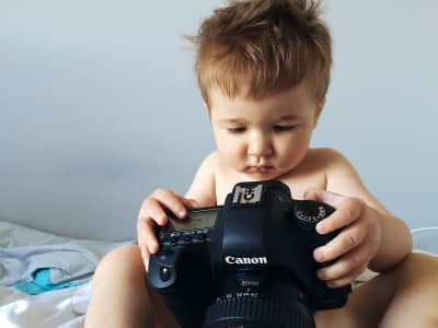 Little boy playing with camera.