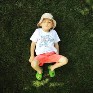 Summer time and happy boy lying on the grass.