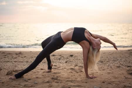Beautiful girl doing yoga asanas in the sand beach.