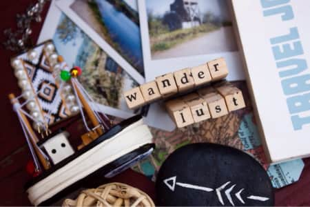 """""""Wanderlust"""" flat lay background with various travel-themed items"""