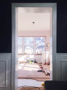 Looking through a doorframe at construction work in progress renovation of sunny room.