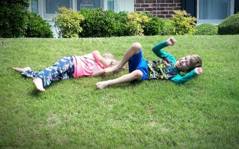 Twins rolling down a hill in their front yard.