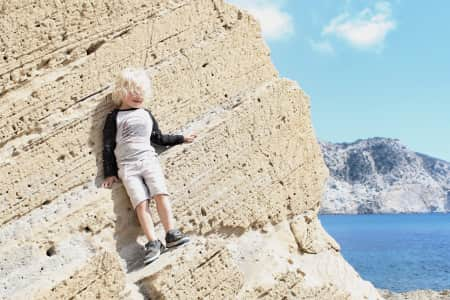 Boy standing on a cliff walk
