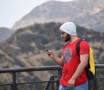 Young millennial with beanie and red shirt using his cellphone to chat outside